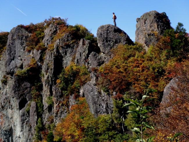 紅葉の岩に立つ